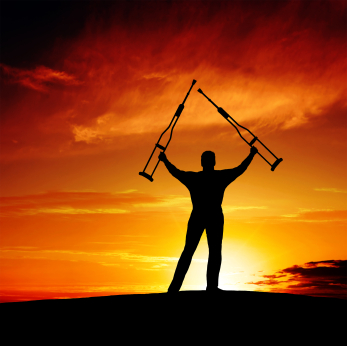 Photo of a silhouetted man with crutches waving his arms triumphantly in the sunset.